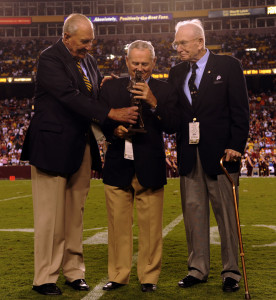Eddie LeBaron, center, is presented with the Lone Sailor Award at FedEx Field in Landover, Maryland, during halftime of a 2010 Washington Redskins-Dallas Cowboys game. LeBaron played for both teams during his NFL career.