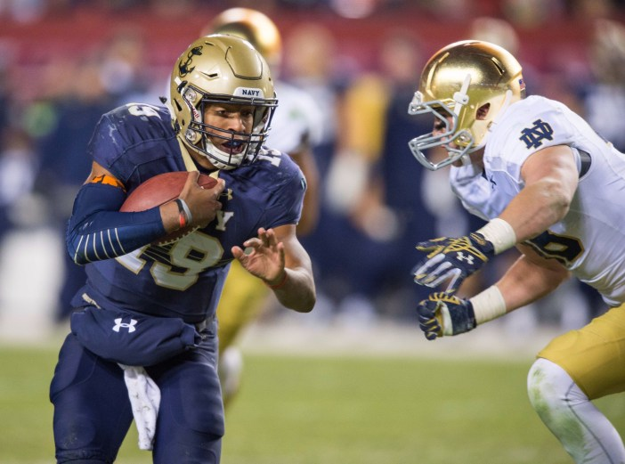 Navy's Keenan Reynolds tries to evade a Notre Dame tackler during last season's Navy-Notre Dame game at FedEx Field, home of the NFL's Washington Redskins. The teams will face off in 2016 in Jacksonville, Florida. (USA Today Sports photo by Matt Cashore)