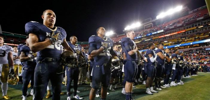 Navy players stand during the playing of the school's alma mater after last year's loss to Notre Dame in Landover, Md. The theme of a respectful rivalry has been part of the lead-up to this year's game, set for Saturday in South Bend. (Associated Press photo by Alex Brandon)