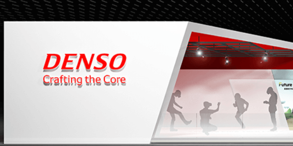 This is an image of a DENSO trade show booth. It is a white booth, with red highlights and says,