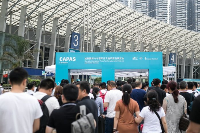 This image shows the entrance to the CAPAS auto show in China. Many people are lined up to enter the show.