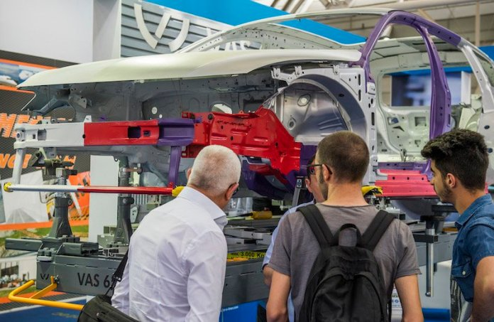 Autopromotec show attendees view a breakdown of a vehicle.