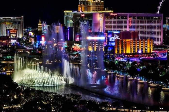 This image shows the brightly lit Las Vegas Strip. To the left are streams of water from a hotel fountain. The photo was taken at night.
