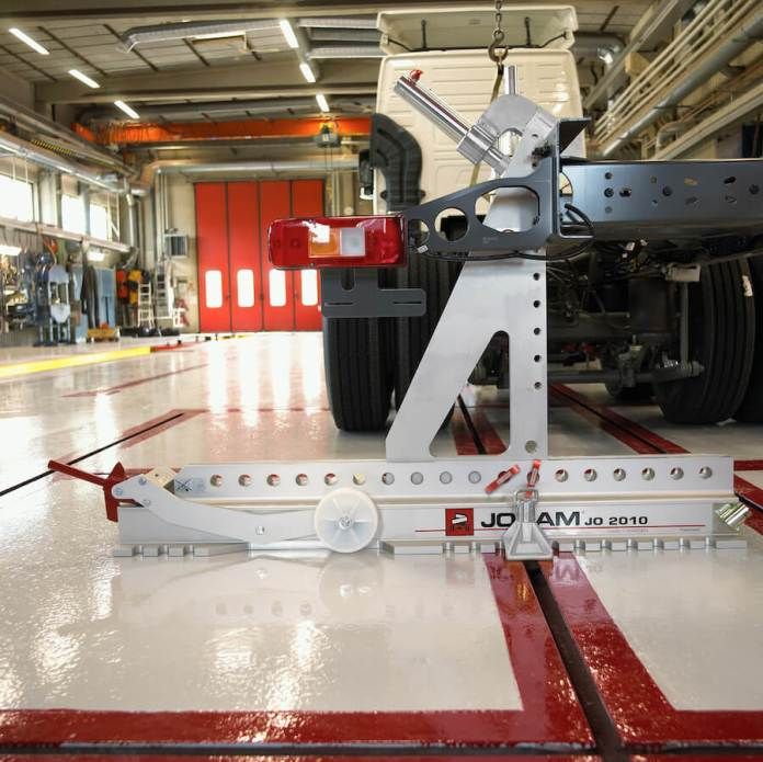 "This image shows a frame-straightening device sitting on a repair shop floor and attached to the rear of a heavy-duty vehicle. The device says ""Josam JO 2010."" The repair shop floor is shiny and the device is situated inside the red-highlighted notches in the floor."