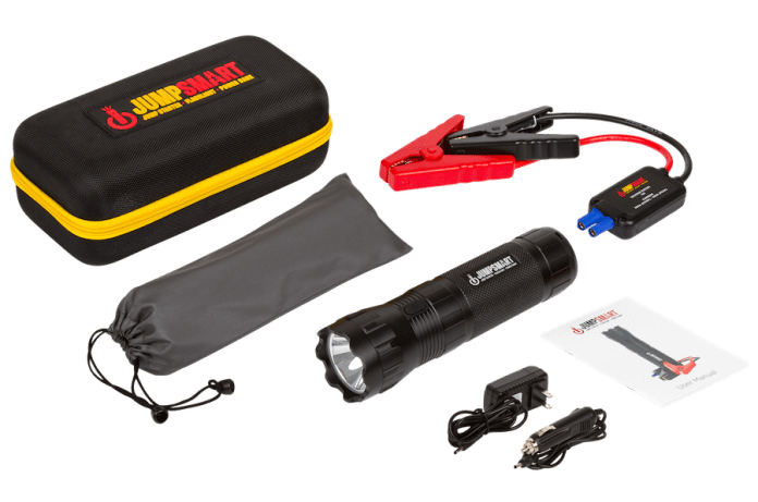 This is an image of the JumpSmart package. All components are laid out on a white background. Show are the unit, which looks like a large flashlight, jumper cables, heavy-duty case, car and wall charging adapters and protective sleeve.