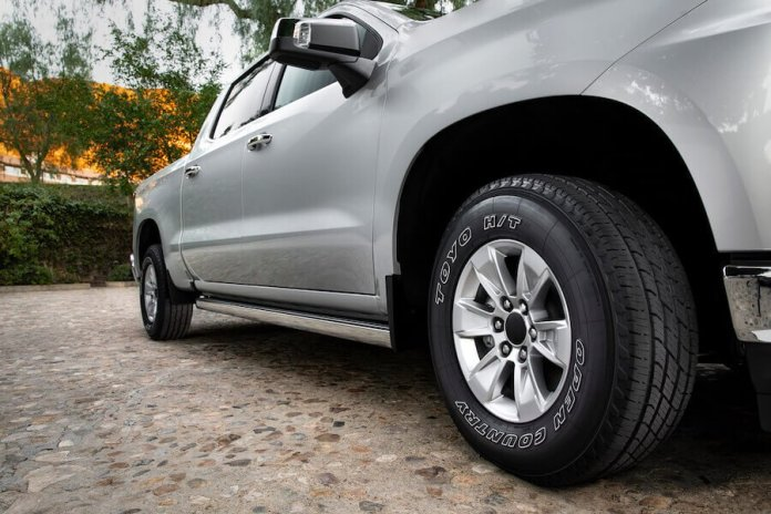 This image shows the all-new Toyo Open Country H/T II tire on a silver-colored truck. The photo is shot from the group up.