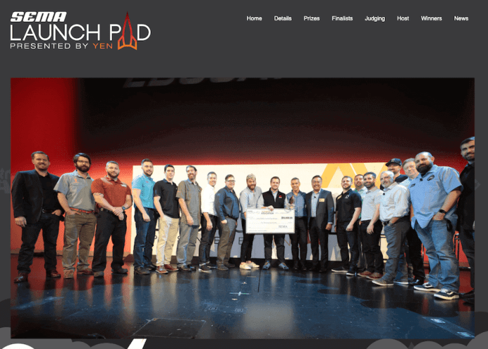 This image shows several people standing on a stage, some are holding an oversized check.