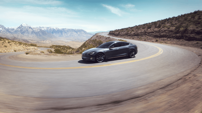 This is a photo of a Tesla Model S taking a curve.