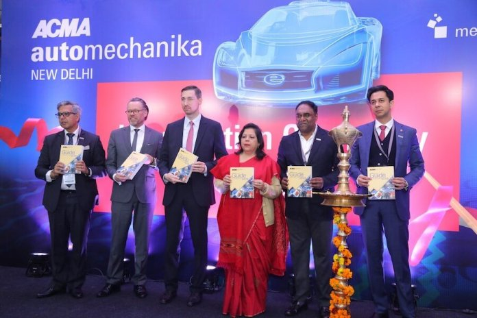 Six dignitaries are shown holding the ACMA Automechanika New Delhi 2019 show guide and smiling at the event.