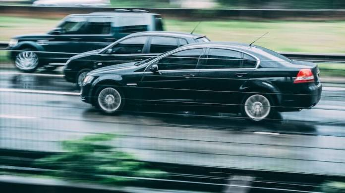 This is a photo of three vehicles driving from right to left on a highway.