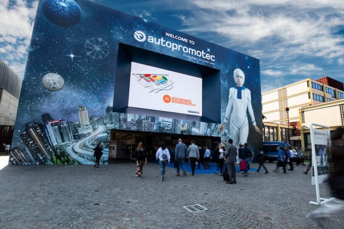 This is the entrance of Autopromotec 2019 in Bologna, Italy. Shown is a sign surrounding the entrance, with a woman in a high-tech looking suit and futuristic images.