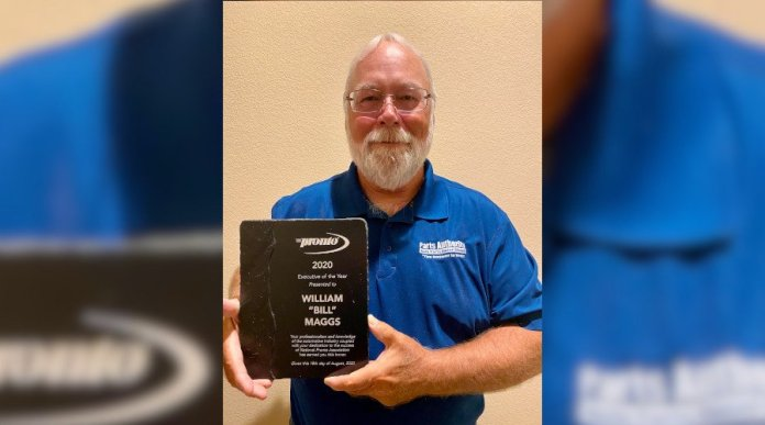 """This is a photo of Bill Maggs. He has a bear and is wearing a blue shirt that says """"Parts Authority."""" He is holding a plaque that says """"Pronto 2020 Executive of the Year presented to William Bill Maggs."""""""