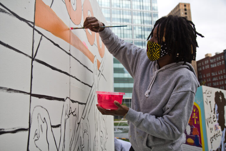 "D'nae Harrison works on her pop-up ""To The Polls"" mural at LOVE Park in Philadelphia. (Kimberly Paynter/WHYY)"