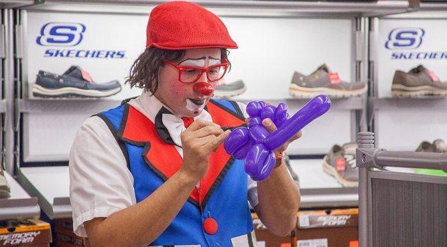 Payaso Che-ché realizando figuras en globos en la tienda Skechers en un evento corporativo