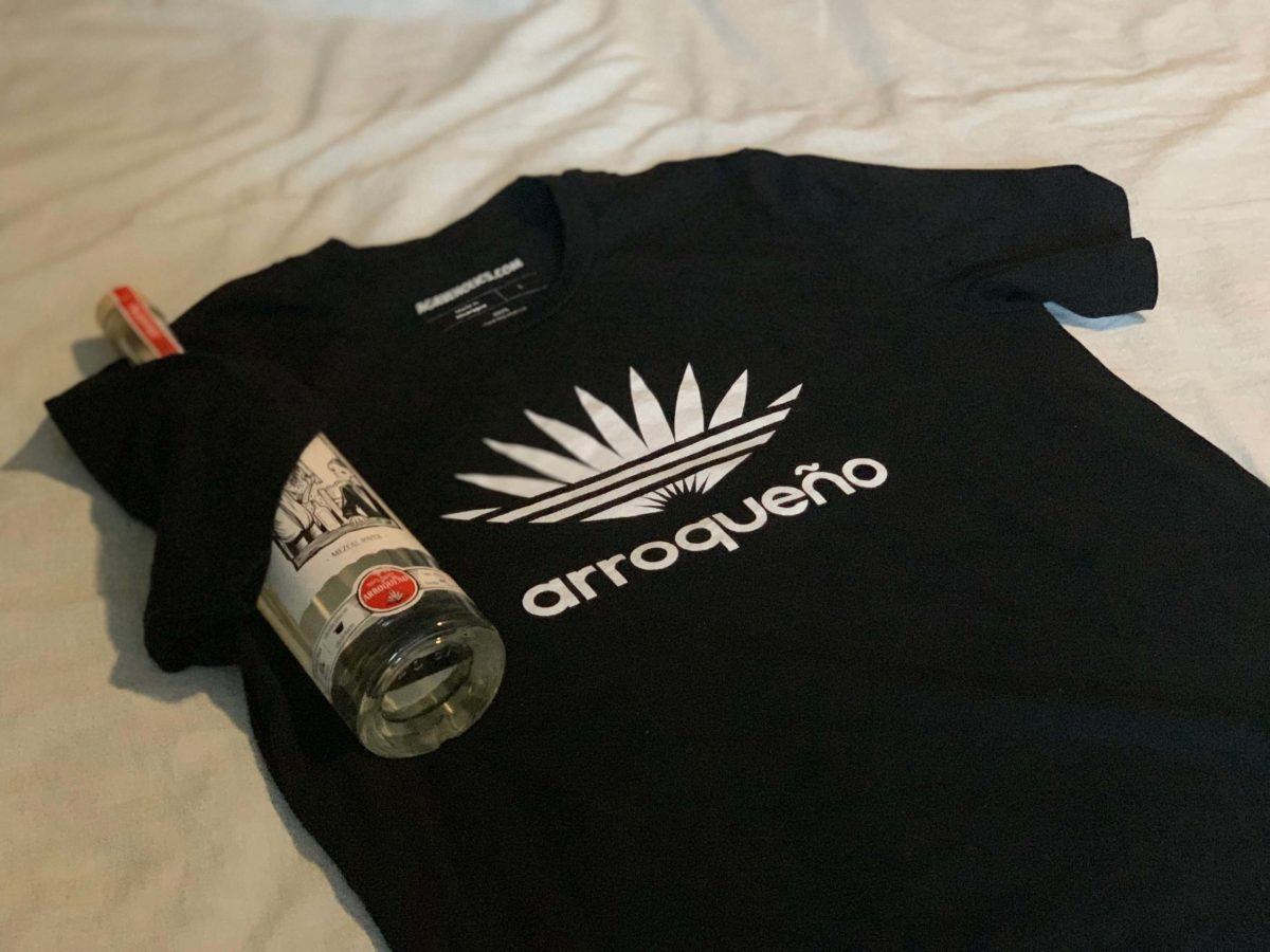 Agaveholics Arroqueño tee shirt laying down with a mezcal bottle next to the shirt
