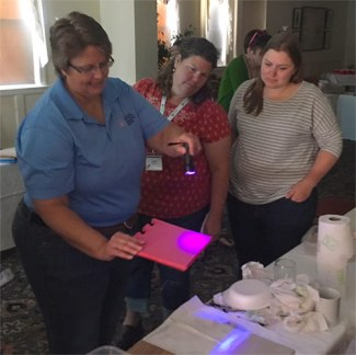 SCRUB Lab: Betsy Greene shining ultraviolet light on disinfected surface
