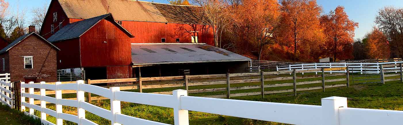 Farm barns and a fence around a pasture