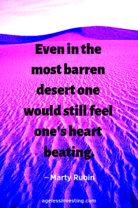 "A pink, blue, and purple desert landscape, with the quote ""Even in the most barren desert one would still feel one's heart beating."" ∼Marty Rubin"