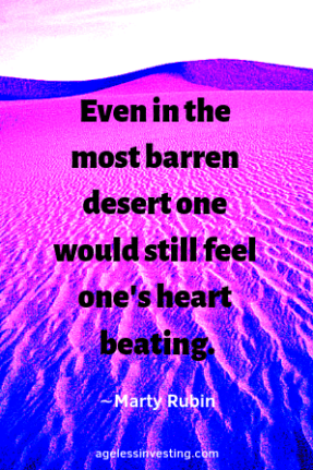 """A pink, blue, and purple desert landscape, with the quote """"Even in the most barren desert one would still feel one's heart beating."""" ∼Marty Rubin"""