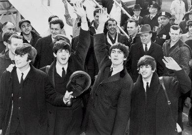 A black and white photo of the Beatles waving to a crowd