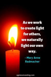 """A candle glowing against a black background, Headline quote, """"As we work to create light for others, we naturally light our own way."""" ∼Mary Anne Radmacher"""