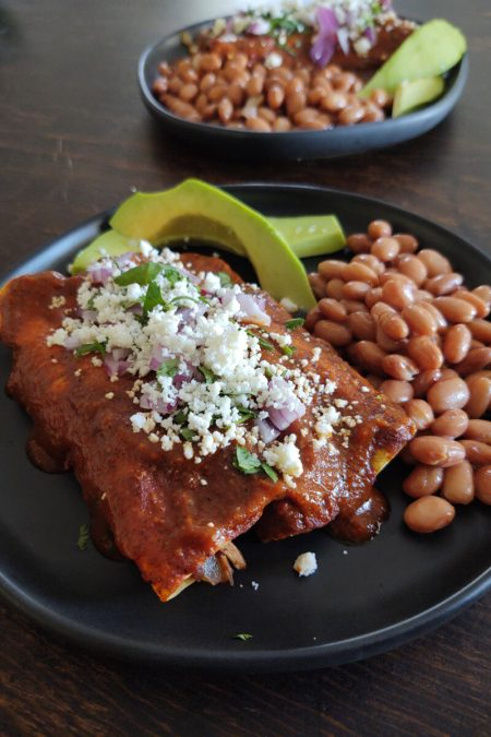 up close dual plated chicken chayote red enchiladas with avocado and beans