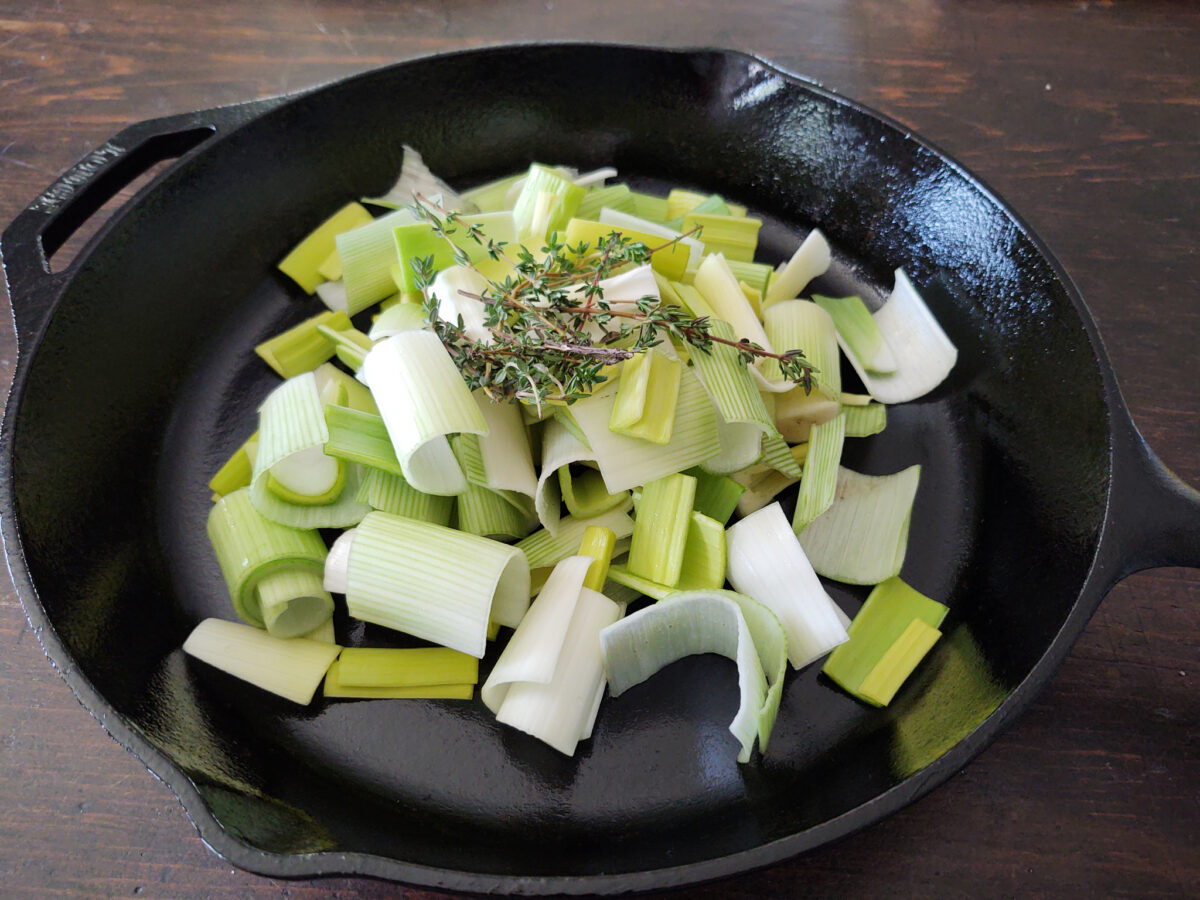 Leeks ready for roasting in a cast iron pan