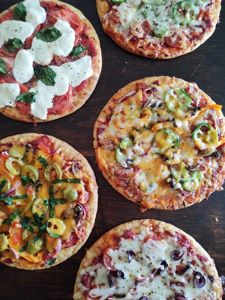 Vertical shot of 5 pita pizzas with 5 minute pizza sauce