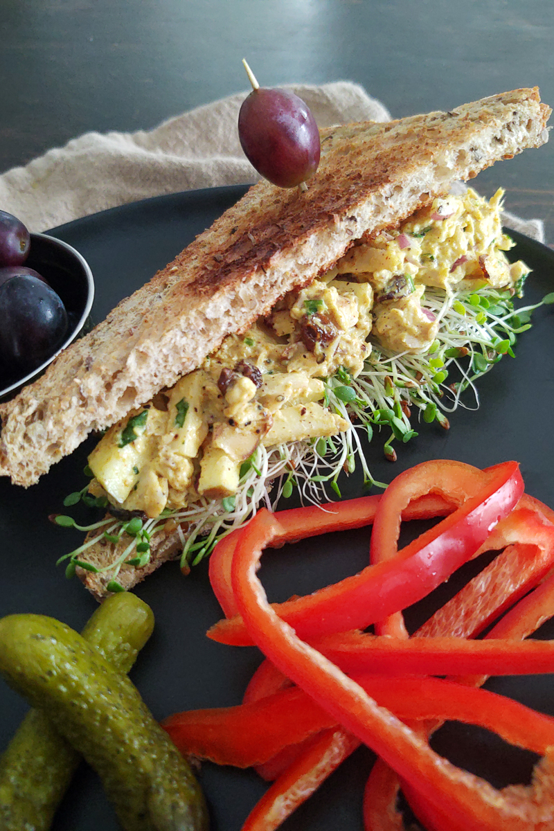 Curry chicken salad sandwich displayed with red bell peppers on a black plate