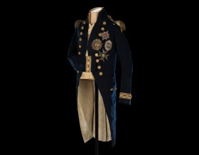 A long dark blue naval coat decorated with gold trim, buttons and medals.