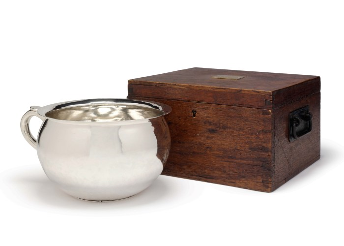 a photo of a silver chamber pot next to a brown wooden box