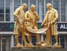 A photograph of a gold statue showing three men dressed in typical Victorian fashion discussing the plans for the railway
