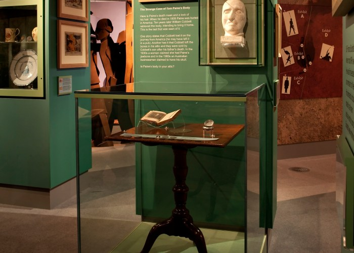 A photograph of the inside of the museum. A small wooden writing desk can be seen in a glass case.