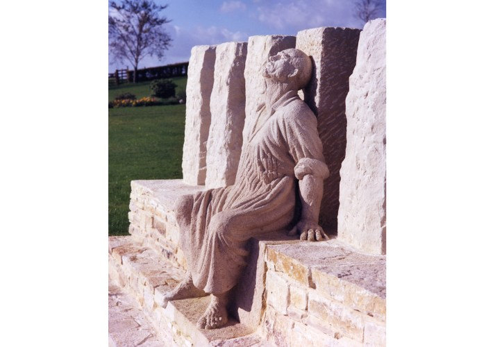 A photograph of the tolpuddle statue showing a seated man dressed in a long basic robe with his head back and eyes closed.