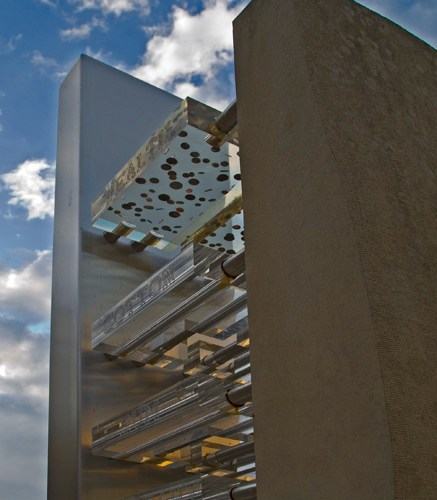 A photograph of the statue taken from below. The photo shows four tiers of clear perspex suspended between two tall towers, one concrete and one metal. A blue and cloudy sky can be seen in the background.