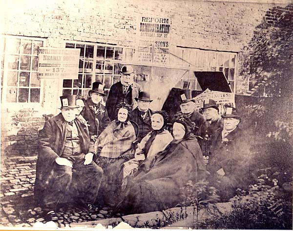 a black and white photo of elderly people in Victorian clothes outside a cottage