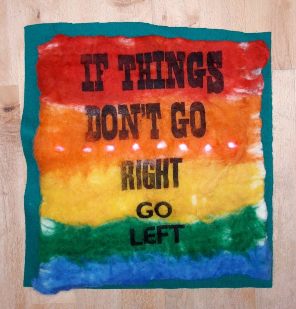 a homemade felt protest banner reading 'if things don't go right go left'