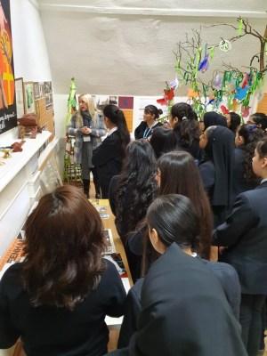 schoolgirls and teacher reading information board in classroom