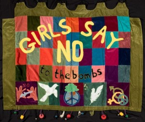 fabric banner with peace symbols reading 'girls say no to the bombs'