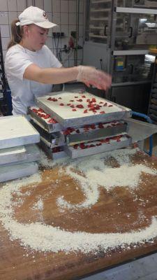 Unsere Konditorin Jennifer streut die Oberhausener Erdeeren des Lepkeshof auf den Käsekuchen