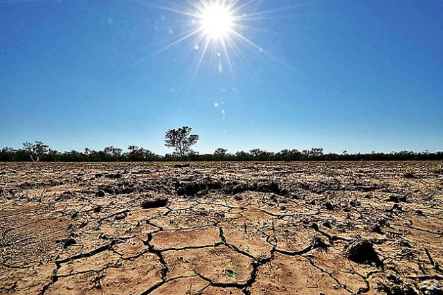 TO GO WITH Australia-weather-drought-farming,FEATURE by Glenda KWEK In this photo taken on February 11, 2015, the sun scorches an already cracked earth on a farm in the Australian agricultural town of Walgett, 650 kilometres (404 miles) northwest of Sydney.  The Australian agricultural town -- which takes its name from the Aboriginal word meaning the meeting of two rivers -- is in the grip of the worst drought in a century, with disillusioned farmers battling to stay afloat.       AFP PHOTO / Peter PARKS
