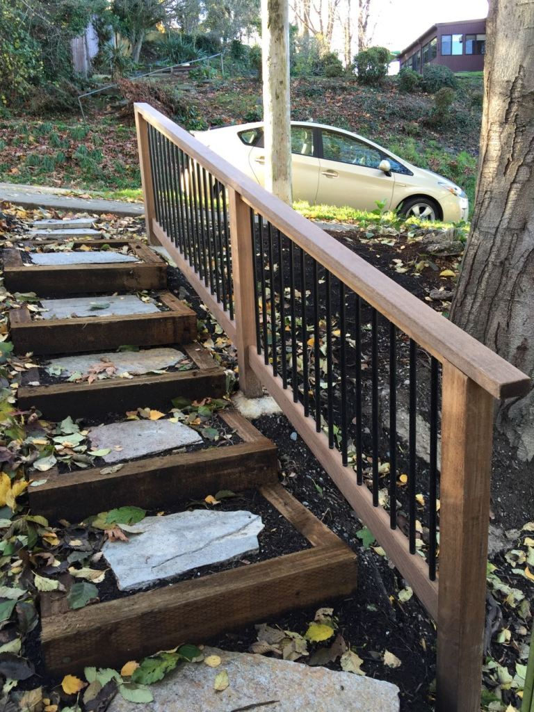 Pressure-treated steps and flagstone pavers placed on the ground, plus an ipe handrail with round aluminum balusters powder coated black.
