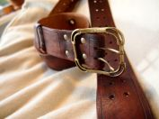Aged and distressed brown belt with brass hardware