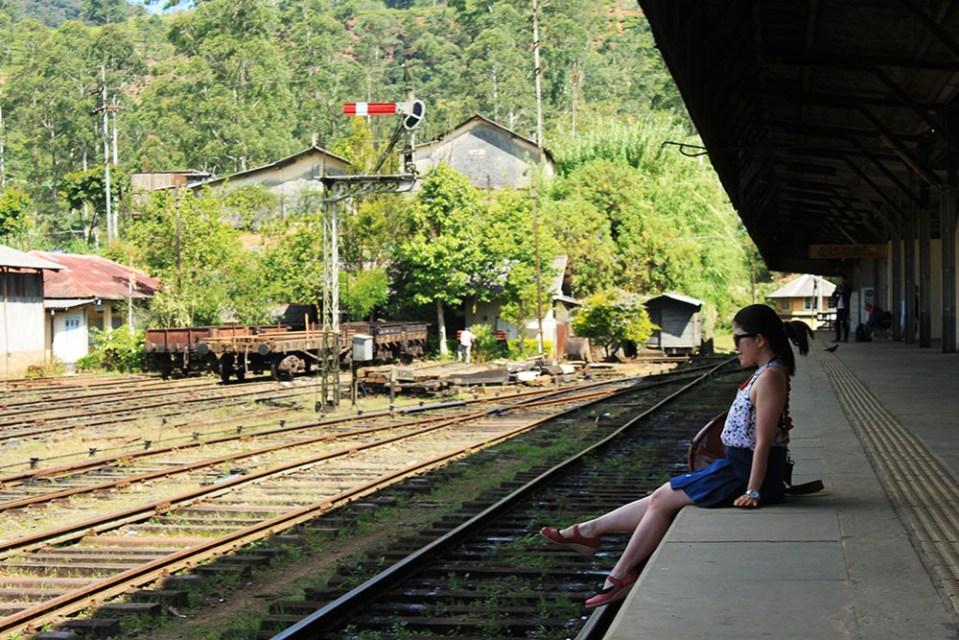 female traveller sitting at nuwara eliya sri lanka train station