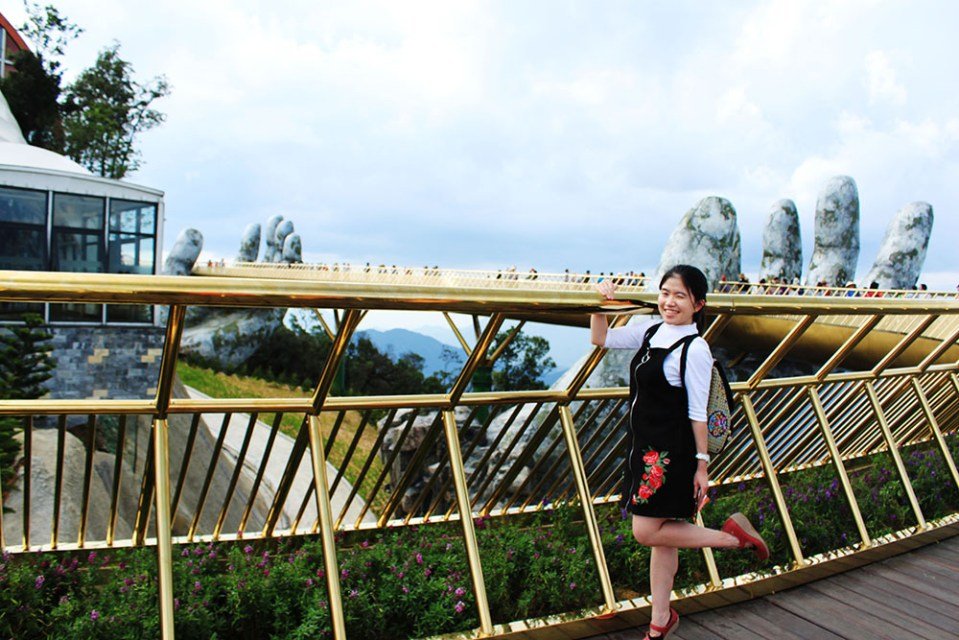 a girl at the golden bridge with God's hands at ba na hills vietnam