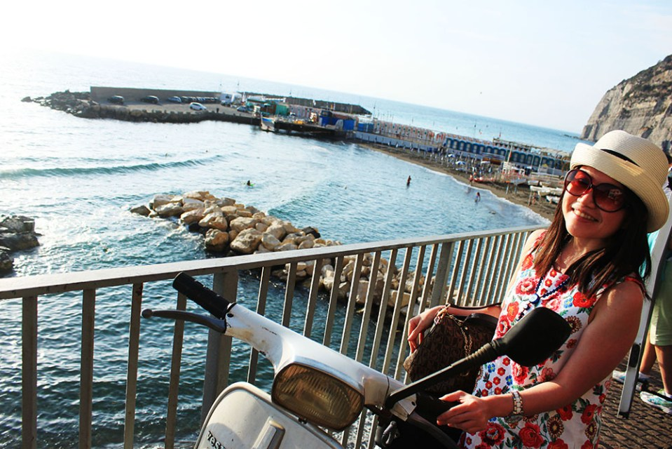 Asian girl with flowery dress and Vespa in her summer holiday in Sorrento, Italy