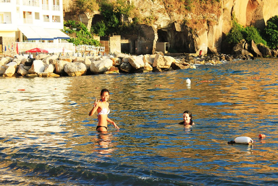 Female travellers swimming in Sorrento beach, Italy during summer holiday