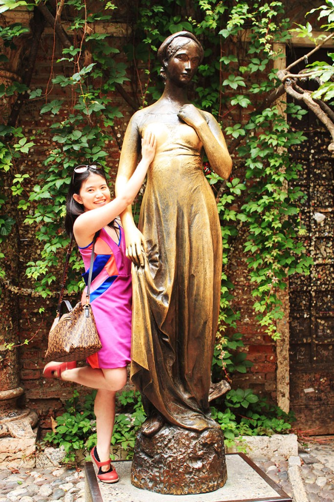 female tourist touches juliet statue's right breast for love luck