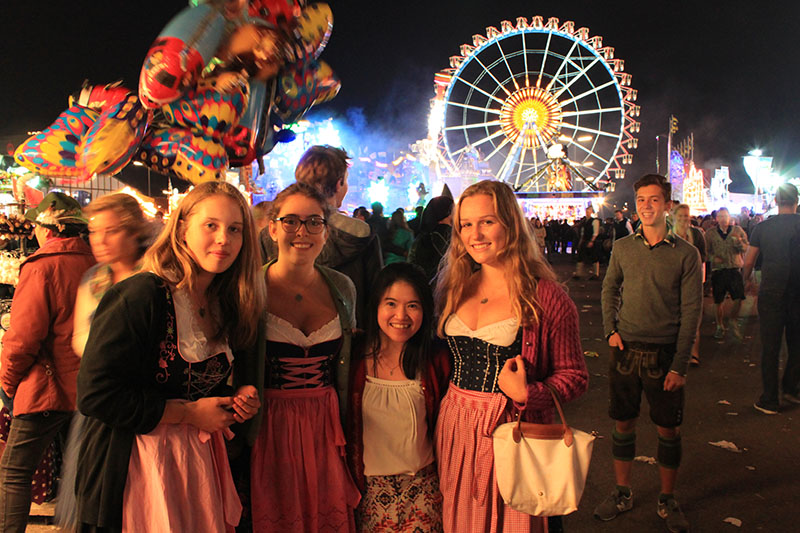 asian european travelers bavarian traditional costume oktoberfest luna park at night munich germany merry go round