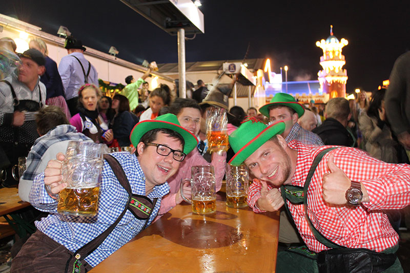 men checkers shirt green hat drinking beer oktoberfest luna park at night munich germany